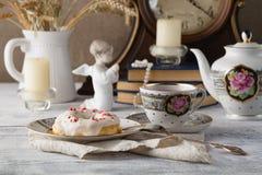 Frühstück mit Donut und Tasse Tee Alte Bücher auf Tabelle Stockfotografie