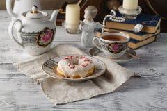 Frühstück mit Donut und Tasse Tee Alte Bücher auf Tabelle Lizenzfreie Stockfotografie
