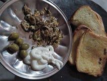 FRÜHSTÜCK mit Ei πtted grünen Oliven lizenzfreies stockbild