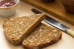 Frühstück mit gesundem Schwarzbrot und konserviertem Stau lizenzfreie stockfotos