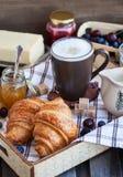 Frühstück mit Hörnchen, Cappuccino und Stau lizenzfreie stockbilder