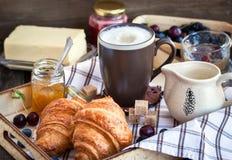 Frühstück mit Hörnchen, Cappuccino und Stau lizenzfreie stockfotos