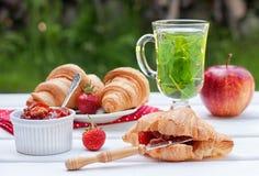 Frühstück mit Hörnchen und Kräutertee Stockfotografie