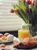 Frühstück mit Hörnchen und Tulpen Stockbild