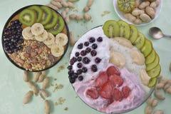 Frühstück mit muesli, acai Blaubeerensmoothie und Kiwi, Früchte auf grünem Hintergrund Gesundes Nahrungsmittelkonzept Flache Lage stockfoto