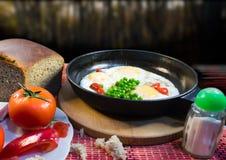 Frühstück mit Spiegeleiern, Erbsen, Tomate, Pfeffer, Salz und Brot auf einem hölzernen Brett stockfoto