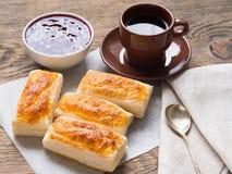 Frühstück von süßen Rollen vom Blätterteig, Himbeermarmelade, Tasse Kaffee auf Pergamentpapier Seitenansicht, Tageslicht Stockfotos