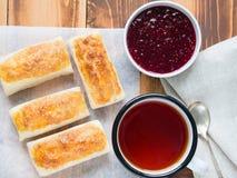 Frühstück von süßen Rollen vom Blätterteig, Himbeermarmelade, Tasse Tee auf Pergamentpapier Lizenzfreie Stockfotos