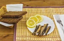 Frühstück von Sprotten mit Zitrone und frischem Schwarzbrot Lizenzfreie Stockfotos