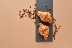 Frühstück von zwei französischen Hörnchen mit Kaffeebohnen Lizenzfreie Stockbilder
