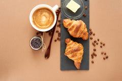 Frühstück von zwei französischen Hörnchen mit Stau und Kaffee Stockbilder