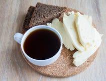 Frühstück: Ziegenkäse und Tasse Kaffee und Scheiben des Roggenbrotes Scheiben des Hüttenkäses auf einem beige Hintergrund Stockfotografie