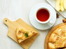 Frühstücken mit Tee und selbst gemachter Kuchen, Apfelkuchen und Apfel auf hölzernem weißem Hintergrund, Draufsicht stockfotografie