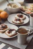 Frühstücken Sie mit dunklem Brot mit Weißkäse und Stau Stockfotos