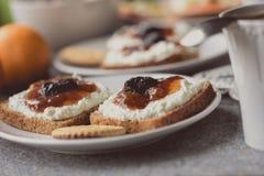 Frühstücken Sie mit dunklem Brot mit Weißkäse und Stau Lizenzfreie Stockbilder