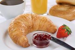 Frühstücken Sie mit einem Hörnchen, einem Kaffee und einem Orangensaft Stockfotos