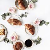 Frühstücken Sie mit Hörnchen, Rosarosenblume, den Blumenblättern, den Weinleseplatten und Zusammensetzung des schwarzen Kaffees Lizenzfreie Stockbilder