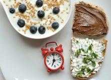 Frühstücken Sie mit Joghurt, Käse und Schokolade auf weißer Tabelle Stockbilder