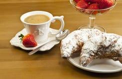 Frühstücken Sie mit Kaffee, frischen Hörnchen und Erdbeeren. Stockbilder