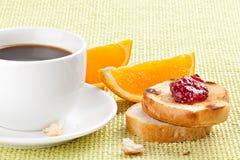 Frühstücken Sie mit Kaffee, Toast, Kirschmarmelade und Orange Lizenzfreies Stockbild
