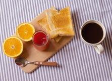 Frühstücken Sie mit Kaffee, Toast, Orangen und Erdbeermarmelade Lizenzfreie Stockbilder
