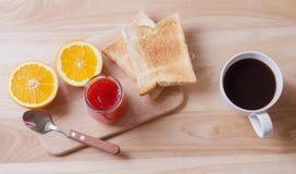 Frühstücken Sie mit Kaffee, Toast, Orangen und Erdbeermarmelade auf Holztisch Stockfotografie
