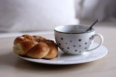 Frühstücken Sie mit Kaffee und frischem Kranz mit Zimt auf Holztisch Unscharfer Hintergrund Lizenzfreie Stockfotos