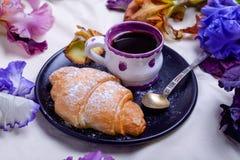 Frühstücken Sie mit süßen Hörnchen und Kaffee auf dem Schwarzblech, das mit Irisblumen im Bett umgeben wird Konzept des gutenmorg Stockbild