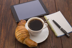 Frühstücken Sie mit Schale des schwarzen Kaffees, der Hörnchen und des Notizbuches lizenzfreies stockbild