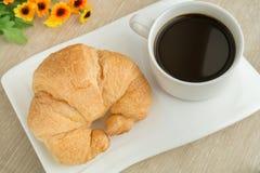 Frühstücken Sie mit Schale des schwarzen Kaffees und des Hörnchens Lizenzfreies Stockbild