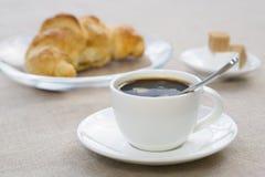Frühstücken Sie mit Schale des schwarzen Kaffees und des Hörnchens Stockfoto