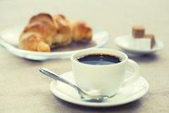 Frühstücken Sie mit Schale des schwarzen Kaffees und des Hörnchens Lizenzfreie Stockbilder
