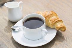 Frühstücken Sie mit Schale des schwarzen Kaffees und des Hörnchens Lizenzfreie Stockfotos