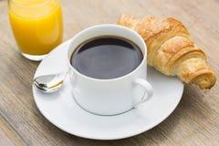 Frühstücken Sie mit Schale des schwarzen Kaffees und des Hörnchens Stockbilder