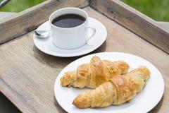 Frühstücken Sie mit Schale des schwarzen Kaffees und des Hörnchens Lizenzfreie Stockfotografie