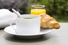 Frühstücken Sie mit Schale des schwarzen Kaffees und des Hörnchens Stockfotos