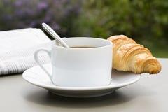 Frühstücken Sie mit Schale des schwarzen Kaffees und des Hörnchens Stockbild