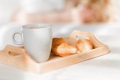 Frühstücken Sie mit Schale schwarzem Kaffee und Hörnchen stockbild