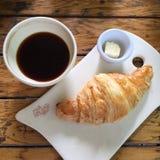Frühstücken Sie mit schwarzem Kaffee und einem Hörnchen mit Butter Lizenzfreie Stockbilder