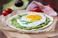 Frühstücken Sie mit Spiegelei und Soße der Avocado auf gegrilltem Mehl Stockbild