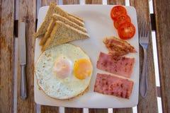 Frühstücken Sie mit Spiegeleiern, Speck, Schinken, Toast, Tomate Lizenzfreie Stockfotografie