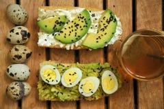 Frühstücken Sie mit Tee- und Avocadosandwich mit Wachteleiern Stockfotografie