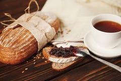 Frühstücken Sie mit Tee und dunklem Brot mit Stau Lizenzfreie Stockfotos