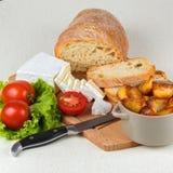 Frühstücken Sie vom Brot, Käse, Tomaten, Kartoffeln und ganz über Salat auf einem Holztisch Lizenzfreie Stockbilder