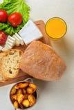 Frühstücken Sie vom Brot, Käse, Tomaten, Kartoffeln und ganz über Salat auf einem Holztisch Stockbild