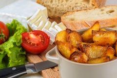 Frühstücken Sie vom Brot, Käse, Tomaten, Kartoffeln und ganz über Salat auf einem Holztisch Lizenzfreie Stockfotos