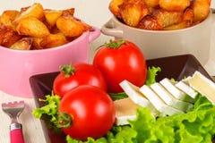 Frühstücken Sie vom Käse, Tomaten, Kartoffeln und ganz über Salat auf einem Holztisch Lizenzfreies Stockfoto