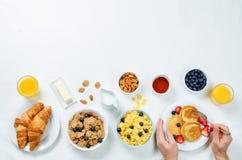 Frühstücksgedeck mit Flocken, Saft, Hörnchen, Pfannkuchen lizenzfreies stockbild