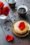 Frühstückskaffee und -pfannkuchen auf dem Tisch mit Rosen Stockfoto