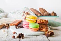Frühstückskost aus Getreide, Plätzchen, Nüsse, Trockenfrüchte und bunte Makronen Stockbilder